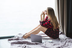 Attractive thoughtful female sitting on floor and looking through window Royalty Free Stock Photos