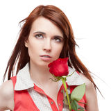 Attractive thoughtful girl holding red rose Stock Image
