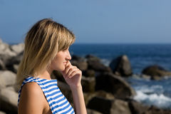 Attractive thoughtful girl rocky beach by the sea. Royalty Free Stock Photos