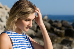 Attractive thoughtful girl rocky beach by the sea. Stock Images