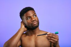Attractive thoughtful guy is standing with brush for teeth royalty free stock image