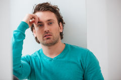 Attractive thoughtful handsome man sitting and thinking Stock Photos