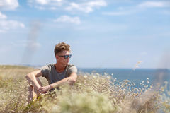 A charming young man on a cliff of a blue sea. A male relaxing on a natural background. Rest concept. Copy space. An attractive and thoughtful man is sitting on Stock Photo