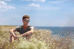 A charming young man on a cliff of a blue sea. A male relaxing on a natural background. Rest concept. Copy space. An attractive and thoughtful man is sitting on Stock Photos
