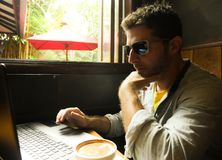 Attractive thoughtful and pensive millennial man working from internet coffee shop with laptop computer thinking relaxed as entrep royalty free stock photo