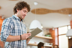 Attractive thoughtful smiling curly young male using tablet at home. Attractive thoughtful smiling curly young male in plaid shirt using tablet at home Stock Images
