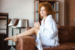 Attractive thoughtful woman in white bathrobe sitting on brown sofa Stock Images