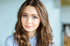 Attractive thoughtful young curly woman looking camera Stock Images