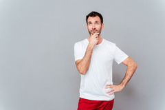 Attractive thoughtful young man in white shirt looking Stock Images