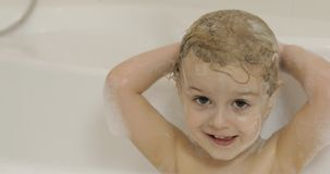 Attractive three years old girl takes a bath. Cleaning and washing hair stock photo