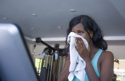 Attractive tired black afro American woman training at fitness club holding towel drying sweat exhausted and sweaty in treadmill. Gym portrait of young royalty free stock images