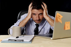 Attractive tired businessman in shirt and tie tired overwhelmed heavy work load exhausted at office Stock Photography