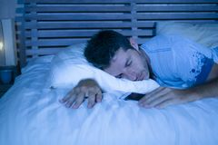 Attractive tired man in bed falling asleep while using mobile phone still holding the cellular in his hand while sleeping in inter. Young attractive tired man in Stock Photography