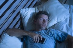 Attractive tired man in bed falling asleep while using mobile phone still holding the cellular in his hand while sleeping in inter. Young attractive tired man in Royalty Free Stock Image