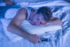 Attractive tired man in bed falling asleep while using mobile phone still holding the cellular in his hand while sleeping in inter. Young attractive tired man in Stock Photo