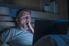 Attractive tired and stressed workaholic man working late night exhausted on bed busy with laptop computer yawning feeling sleepy royalty free stock photo