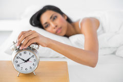 Attractive tired woman turning off the alarm clock. Lying in her bed Stock Images