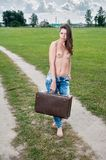 Attractive topless woman with suitcase. Pretty naked woman going on road with old suitcase Royalty Free Stock Photo