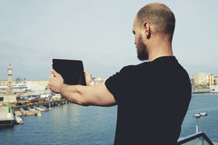 Attractive tourist with digital tablet camera taking picture of beautiful city from viewpoint Stock Photography