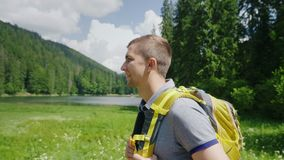 An attractive tourist man goes to a picturesque place in the background of meadows, mountains and sky. Tourism and. Man goes to a picturesque place in the stock video
