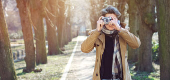 Attractive Tourist taking a photograph with vintage camera Royalty Free Stock Photography