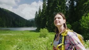 An attractive tourist woman goes to a picturesque place in the background of meadows, mountains and sky. Tourism and. Active lifestyle. Steadiam shot stock footage