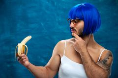 Attractive transsexual person wearing blue wig. And female cloth eats banana. Place for text Royalty Free Stock Images