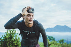 Attractive Traveler vith GoPrO camera on his hand against the Ba Royalty Free Stock Images