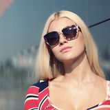 Attractive trendy girl. Beautiful attractive trendy girl with sunglasses posing on the background wall mirror Royalty Free Stock Images