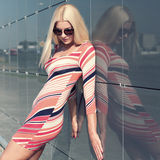 Attractive trendy girl. Beautiful attractive trendy girl with sunglasses posing on the background wall mirror Royalty Free Stock Photo