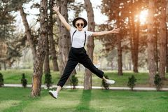 Attractive trendy happy hipster young woman in hat and sunglasses have fun in the park at the sunset. Freedom concept. Stock Photo