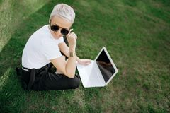 Attractive trendy happy hipster young woman with notebook in hat and sunglasses have fun in the park on the grass. Stock Photo