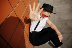 Attractive trendy hipster young woman with stylish red sunglasses and black hat stay near wall. Royalty Free Stock Images