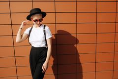 Attractive trendy hipster young woman with stylish red sunglasses and black hat stay near wall. Stock Photos