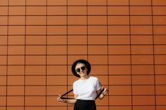 Attractive trendy hipster young woman with stylish sunglasses and black hat stay near wall. Stock Photo