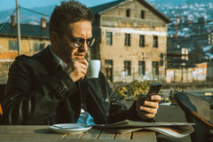 Attractive trendy male model drinking coffee and looking in phon Royalty Free Stock Images