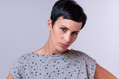 Attractive trendy woman with short dark hair. Tilting her head to the side as she stares thoughtfully at the camera over grey royalty free stock photo