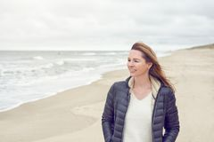 Attractive trendy woman walking on a deserted sandy beach. On a cloudy day at low tide turning to smile at the camera with copy space royalty free stock photos