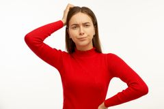 Attractive trendy young female freelancer looking away with confused disappointed expression, scratching head stock photos