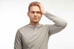 Attractive trendy young male freelancer with beard looking away with confused disappointed expression, scratching head royalty free stock images