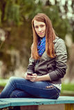 Attractive trendy young woman sitting on a bench stock images