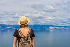 Attractive tween tourist girl in hat and backpack standing on cliff top and admiring beautiful landscape of blue sky and Baikal stock image