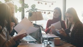 Attractive two businesswoman discussing document and using a laptop at coffee shop. Four businesswoman working together about documents, partner discuss plan or stock video