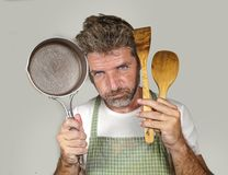 Attractive unhappy and overwhelmed home cook man in apron holding spoon and pan feeling upset and lazy  in domestic work and. Lifestyle portrait of young royalty free stock photo
