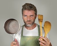 Attractive unhappy and overwhelmed home cook man in apron holding spoon and pan feeling upset and lazy  in domestic work and. Lifestyle portrait of young stock photography