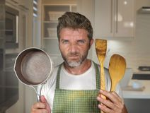 Attractive unhappy and overwhelmed home cook man in apron holding spoon and pan feeling upset and lazy at house kitchen in. Lifestyle portrait of young stock photos