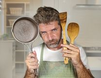 Attractive unhappy and overwhelmed home cook man in apron holding spoon and pan feeling upset and lazy at house kitchen in. Lifestyle portrait of young stock image