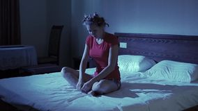 Attractive unhappy young woman in bed. Young attractive girl in red t-shirt sitting on a bed in the room the night and complained curls face stock footage