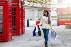 City shopping woman walks along red telephone booths in London, UK royalty free stock photography