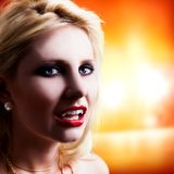 Attractive vampire in front of light background. Attractive vampire in front of bright light background Stock Image